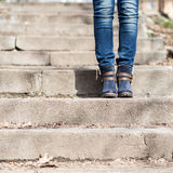 Female legs in winter boots and jeans on stairs Stock Photography