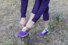 Female legs. Woman in dark violet sportswear ties bright lilac sneakers with lime shoelaces, preparing for a jog, run or other fit royalty free stock photos