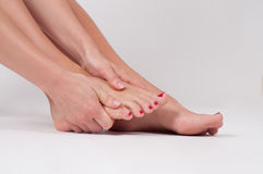 Female legs. Woman massaging her foot stock images