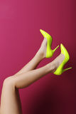 Female legs. With yellow high heels on a pink background Stock Photo