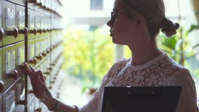 Woman searching card database cabinet at the library. Female librarian searching card database cabinet at the library stock footage