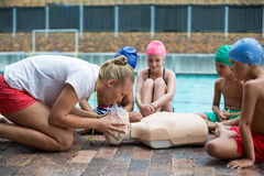 Female Lifeguard Demonstrating Children During Rescue Training Royalty Free Stock Images