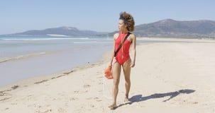 Female lifeguard walking along beach Stock Photo