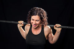 Female Lifter With Barbell Eyes Closed Laughing. A female weight lifter, holding a barbell on her shoulders, laughs with eyes closed. She looks like she is stock images