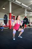 Female Lifting Heavy Barbell In Gym. Determined female lifting heavy barbell in gym Royalty Free Stock Images