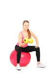 Female lifting up a dumbbell seated on a ball Royalty Free Stock Photos