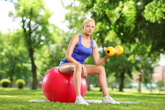 Female lifting weigth and sitting on an exercise ball in park Royalty Free Stock Photos