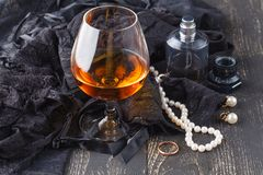 Female lingerie and accessories with glass of cognac Royalty Free Stock Photography