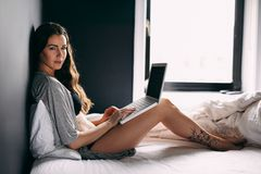 Female in lingerie on bed with a laptop Royalty Free Stock Photography