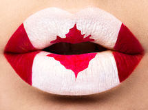 Female lips close up with a picture flag of Canada. Red, white, maple leaf Royalty Free Stock Image