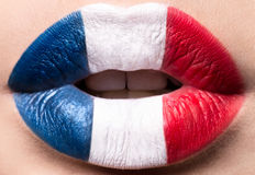 Female lips close up with a picture flag of France. Blue, white, red. Female lips close up with a picture of the flag of France. Blue, white, red royalty free stock photo