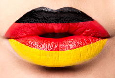 Female lips close up with a picture flag of Germany. black, red, yellow. Royalty Free Stock Photography