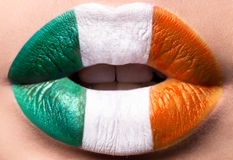Female lips close up with a picture flag of Ireland. Green, white, Orange. Royalty Free Stock Images