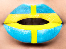 Female lips close up with a picture flag of Sweden.  blue, yellow Royalty Free Stock Photo