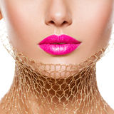 Female lips with pink lipstick and golden veil on the neck. clos Stock Photo