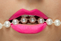 Female lips with pink lipstick and pearls thread. Stock Images