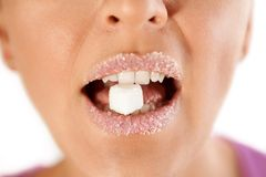 Female lips with sugar biting cube stock images