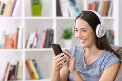 Female listening music on line at home. Happy female listening to music on line with a smart phone and headphones sitting on a couch at home Royalty Free Stock Photo