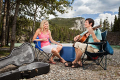 Female listening to man playing guitar. Young woman listening to man playing guitar in forest Royalty Free Stock Photo