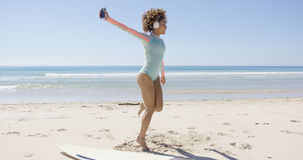 Female listening to music on beach. Female listening to music wearing light blue swimsuit and headphones on beach. Tarifa beach. Provincia Cadiz. Spain Royalty Free Stock Photo