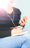 Female listening to music by earphone and look at smartphone in hand with pen in other hand Stock Photography