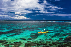 Female and little boy paddling canoe on a lagoon with coral reef. Female and little boy paddling canoe on a lagoon with tropical coral reef stock image