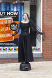 Female Living Statue in Leeds. A girl with ginger hair dressed in a period dress with vale performing as a living statue in Leeds in July 2015 Stock Photo