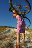 The female logic. The girl bears a bicycle uphill stock photo