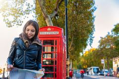Female London tourist looks at a map in front of a red telephone booth. Attractive, female London tourist stands in front of a red telephone booth and looks at a royalty free stock photos