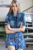 Female with long blond hair. Female with long blond hair in summer dress and jeans jacket royalty free stock image