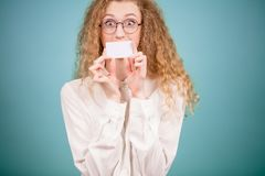 Female with long fair hair is shutting her mouth with sheet of paper. Young female with long fair hair is shutting her mouth with sheet of paper visiting card royalty free stock photos