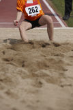 Female long jump competition with woman fallin in the sand Royalty Free Stock Images