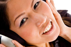 Female looking at camera while listening to music Stock Photography