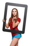 Female looking through the frame blowing a kiss Royalty Free Stock Photography