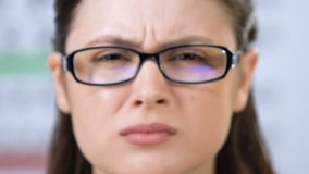 Female looking through glasses with partly closed eyes, vision disorder, problem. Stock footage stock footage
