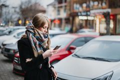 Female looking at mobile device on autumn street young caucasian woman wearing wool scarf coat royalty free stock image