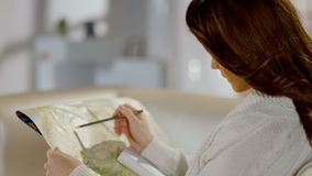 Female looking for place on map, planning road trip with tourist attractions. Stock photo stock images