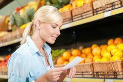 Female looks through shopping list near the heap of fruits Royalty Free Stock Photography