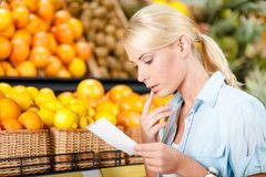 Female looks through shopping list near the stack of fruits Stock Photography