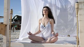 Female in lotus position meditation on bungalow, yoga at beach in summer, wind develops hair and white cloth, tropical stock video