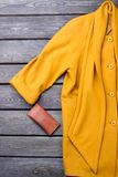 Female luxury yellow overcoat. Women fashion cashmere topcoat and leather purse on old wooden background Royalty Free Stock Photography