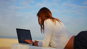 Female lying on a bench near the sea and typing on laptop stock video footage
