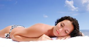 Female lying down on beach under summer sun Royalty Free Stock Photos