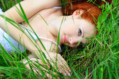 Female lying on grass field stock photo