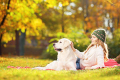 Female lying on a grass with her dog in a park Stock Photos