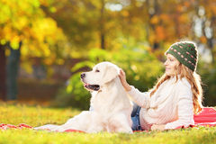 Female lying on grass with her dog in a park Royalty Free Stock Image