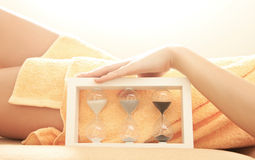 Female lying in spa salon with sandglass Stock Photo