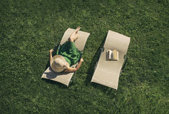 Female lying on sunbed. Woman lying on  sunbed with book and hat Royalty Free Stock Photo
