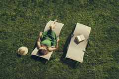 Female lying on sunbed. Woman lying on  sunbed with book and hat Stock Photography