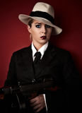 Female mafia-boss. With hat holding a machine-gun Stock Photos